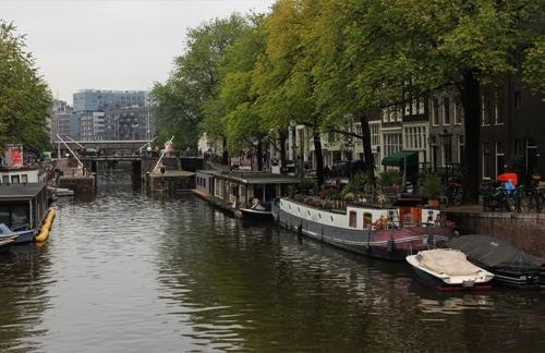 Blick auf eine Gracht mit Schleuse in Amsterdam
