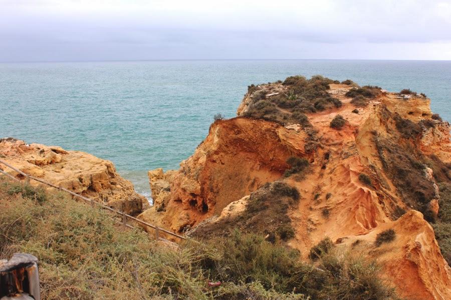 rötliche Felsen vor blauem Meer