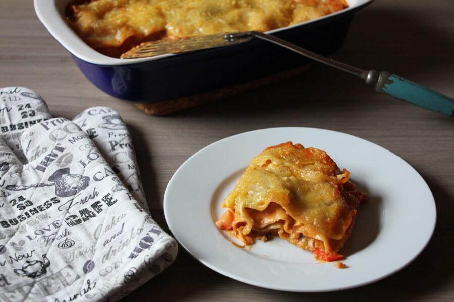 ein Stück vegane Lasagne neben Topfhandschuhen