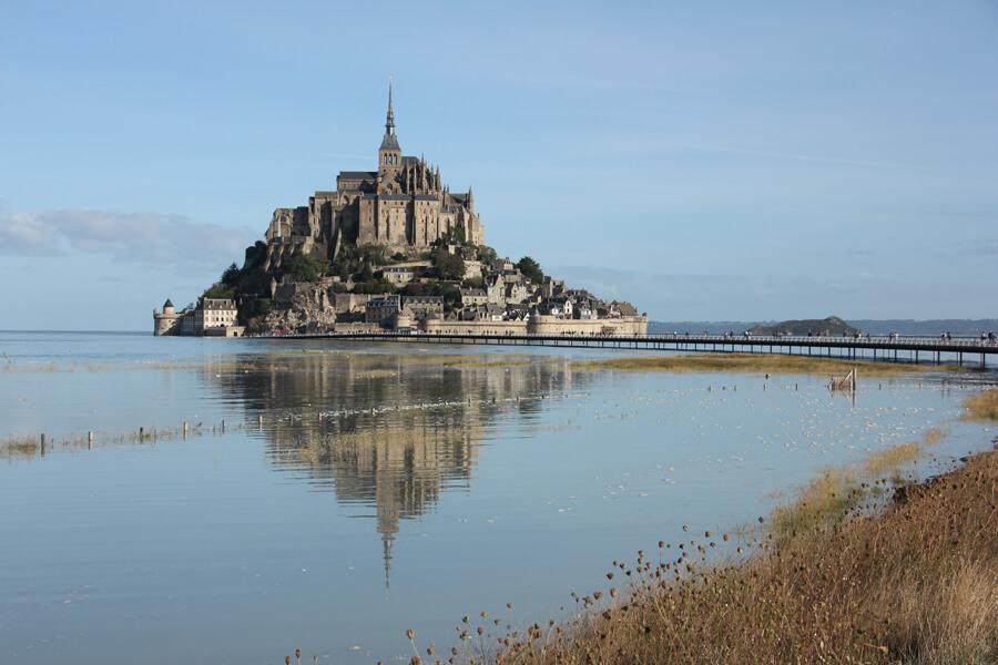 Der Mont St Michel spiegelt sich im Wasser.