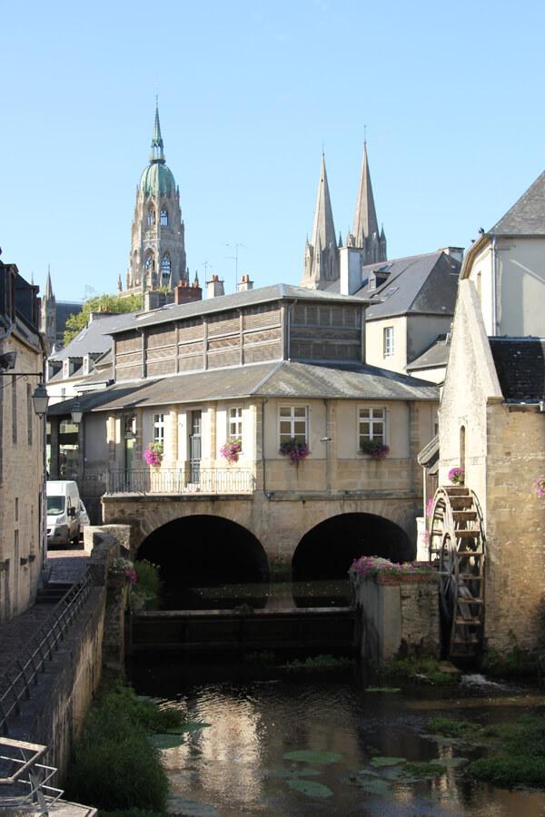 Bayeux Altstadt mit Fluss, Mühlrad und der Kathedrale im Hintergrund