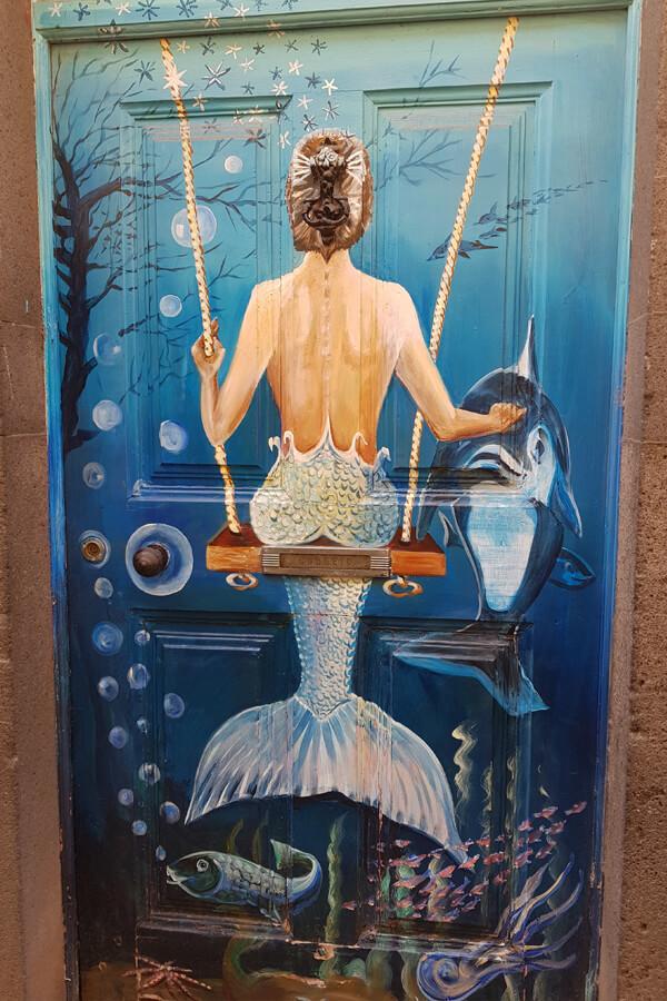 Tür mit Meerjungfrau und Delfin bemalt.