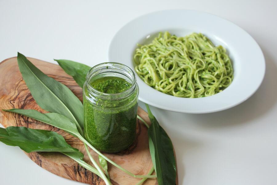 Veganes Bärlauch Petersielien Pesto im Glas neben Spaghettiteller