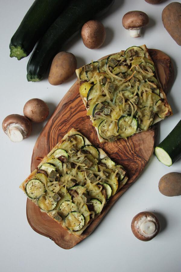 Vegane Blätterteig-Tarte auf Holzbrett mit frischem Gemüse dekoriert